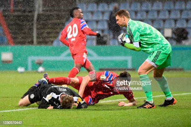 Bayern Munich's German goalkeeper Manuel Neuer saves the ball next to Holstein Kiel's German midfielder Joshua Mees and Bayern Munich's German...