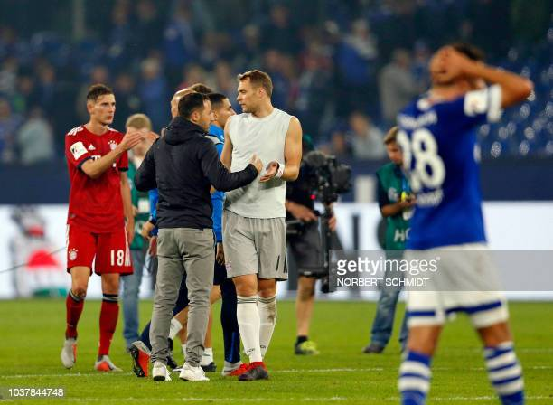 Bayern Munich's German goalkeeper Manuel Neuer speaks with Schalke's German headcoach Domenico Tedesco after the German First division Bundesliga...