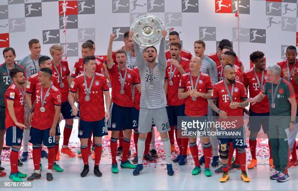 Bayern Munich's German goalkeeper Sven Ulreich lifts the trophy during the celebration for the 28th German football championship after the German...