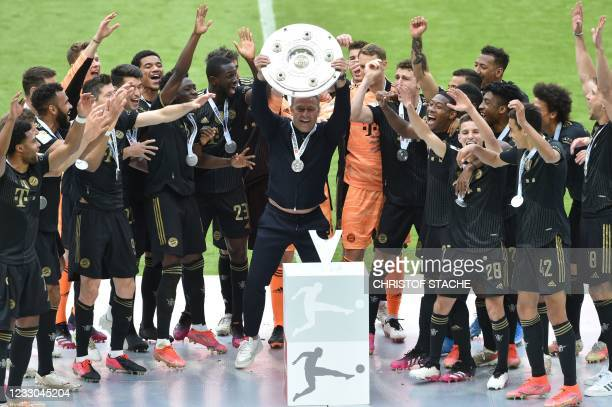 Bayern Munich's German head coach Hans-Dieter Flick and Bayern Munich's team players celebrate with the trophy after the German first division...