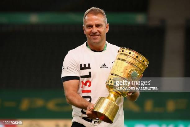 Bayern Munich's German head coach Hans-Dieter Flick celebrates with the German Cup trophy after winning the final football match Bayer 04 Leverkusen...