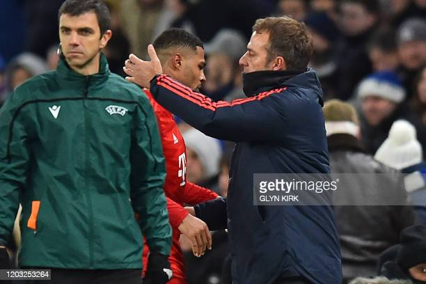 Bayern Munich's German head coach HansDieter Flick congratulates Bayern Munich's German striker Serge Gnabry as he leaves the pitch substituted...