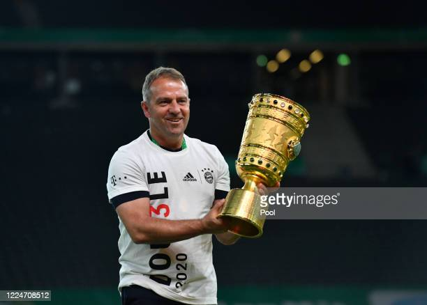 Bayern Munich's German head coach Hans-Dieter Flick holds the German Cup trophy as he celebrates winning the DFB Cup final match between Bayer 04...
