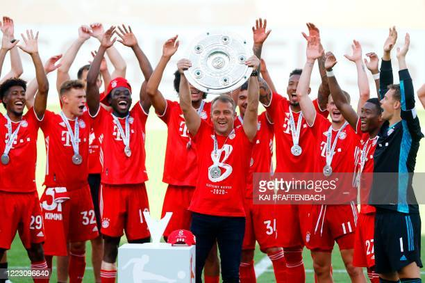 Bayern Munich's German head coach HansDieter Flick lifts the trophy as Bayern Munich players celebrate after the German first division Bundesliga...
