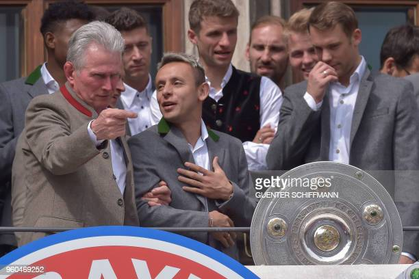 Bayern Munich's German head coach Jupp Heynckes and his players including Brazilian defender Rafinha celebrate on the balcony of the city hall in...