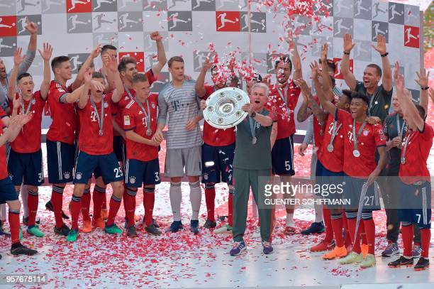 Bayern Munich's German head coach Jupp Heynckes lifts the trophy during the celebration for the 28th German football championship after the German...