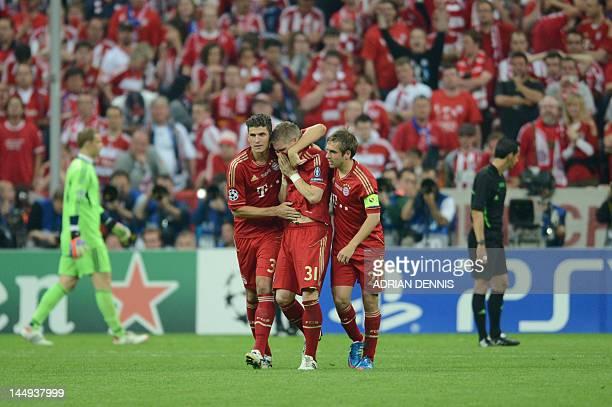 Bayern Munich's German midfielder Bastian Schweinsteiger is comforted by his teammates Bayern Munich's striker Mario Gomez and Bayern Munich's...
