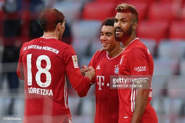 Bayern Munich's German midfielder Jamal Musiala celebrates scoring the 50 goal with his teammate Bayern Munich's German midfielder Leon Goretzka and...