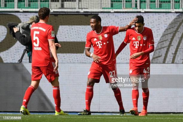 Bayern Munich's German midfielder Jamal Musiala celebrates with teammates Bayern Munich's Austrian defender David Alaba and Bayern Munich's French...