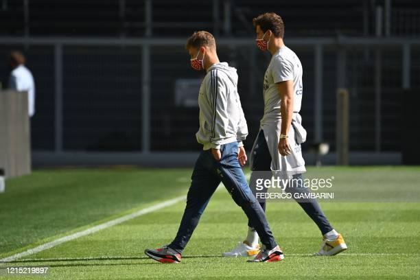 Bayern Munich's German midfielder Joshua Kimmich and Bayern Munich's German midfielder Leon Goretzka wear face protection masks as they walk on the...
