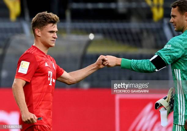 Bayern Munich's German midfielder Joshua Kimmich and Bayern Munich's German goalkeeper Manuel Neuer bump fists after the German first division...