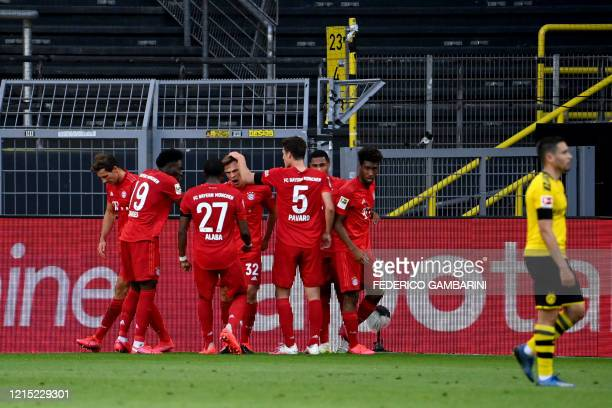 Bayern Munich's German midfielder Joshua Kimmich celebrates scoring with his teammates during the German first division Bundesliga football match BVB...