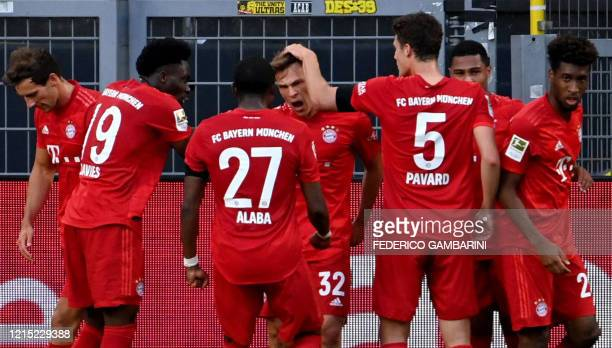 Bayern Munich's German midfielder Joshua Kimmich celebrates scoring with his teammates during the German first division Bundesliga football match BVB...