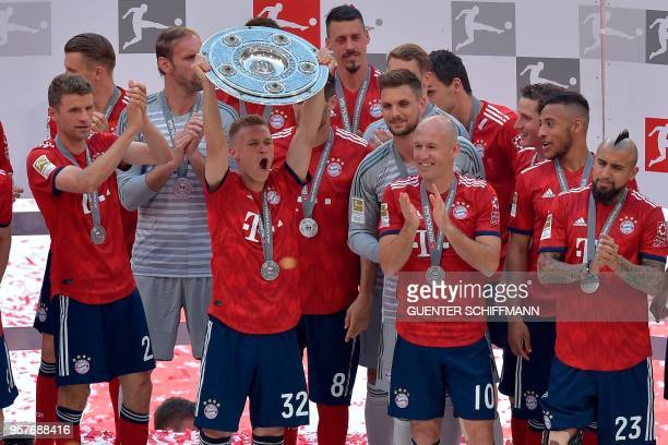 Bayern Munich's German midfielder Joshua Kimmich lifts the trophy at the end of the German first division Bundesliga football match FC Bayern Munich...