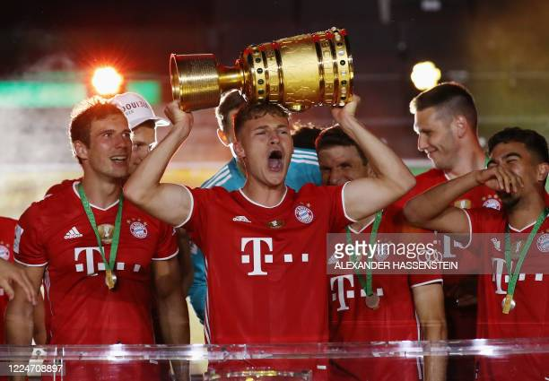 Bayern Munich's German midfielder Joshua Kimmich raises the German Cup trophy as he and his teammates celebrate winning the final football match...