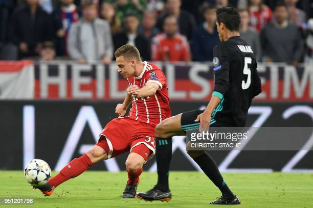 Bayern Munich's German midfielder Joshua Kimmich scores a goal past Real Madrid's French defender Raphael Varane during the UEFA Champions League...