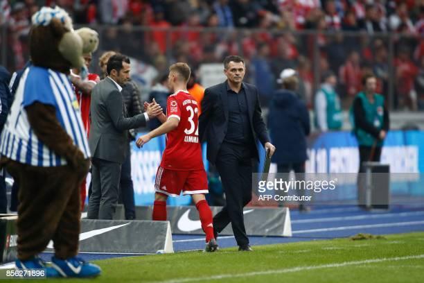 Bayern Munich's German midfielder Joshua Kimmich shakes hands with Bayern Munich's Bosnian sporting director Hasan Salihamidzic next to Bayern...