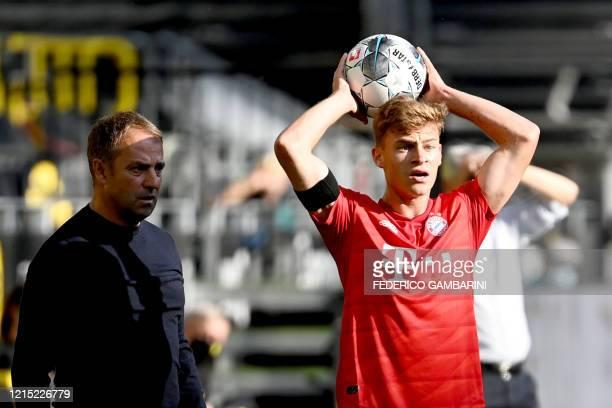 Bayern Munich's German midfielder Joshua Kimmich takes a throw in next to Bayern Munich's German head coach HansDieter Flick during the German first...