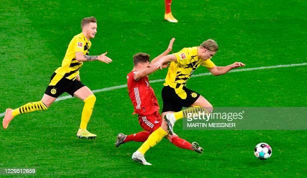 Bayern Munich's German midfielder Joshua Kimmich vies for the ball with Dortmund's German forward Marco Reus and Dortmund's Norwegian forward Erling...