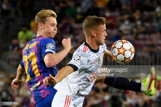 Bayern Munich's German midfielder Joshua Kimmich vies for the ball Barcelona's Dutch midfielder Frenkie De Jong during the UEFA Champions League...