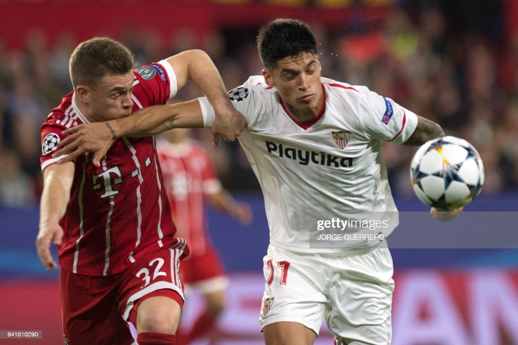 Bayern Munich's German midfielder Joshua Kimmich (L) vies with Sevilla's Argentinian midfielder Joaquin Correa during the UEFA Champions League quarter-final first leg football match between Sevilla FC and Bayern Munich at the Ramon Sanchez Pizjuan Stadium in Sevilla on April 3, 2018. / AFP PHOTO / Jorge GUERRERO