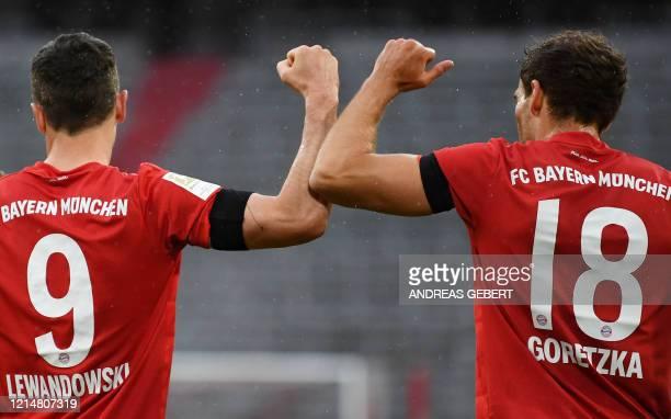 TOPSHOT Bayern Munich's German midfielder Leon Goretzka celebrates scoring the opening goal with Bayern Munich's Polish forward Robert Lewandowski...