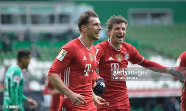 Bayern Munich's German midfielder Leon Goretzka celebrates with Bayern Munich's German forward Thomas Mueller after scoring the 0-1 during the German...