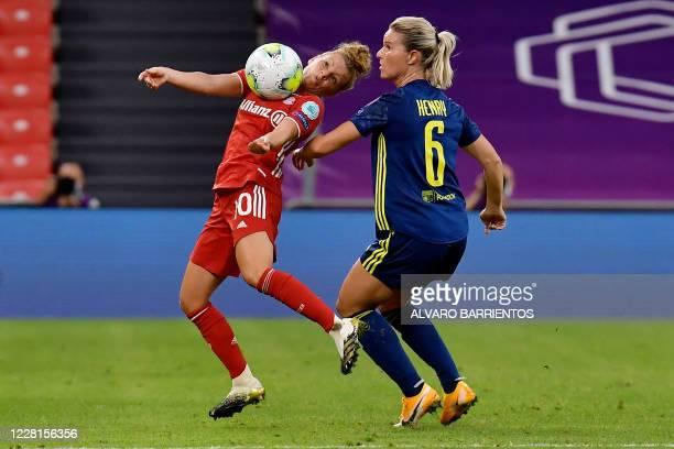 Bayern Munich's German midfielder Linda Dallmann vies with Lyon's French midfielder Amandine Henry during the UEFA Women's Champions League...