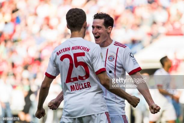 Bayern Munich's German midfielder Sebastian Rudy celebrates scoring his side's third goal with Bayern Munich's German forward Thomas Mueller during...