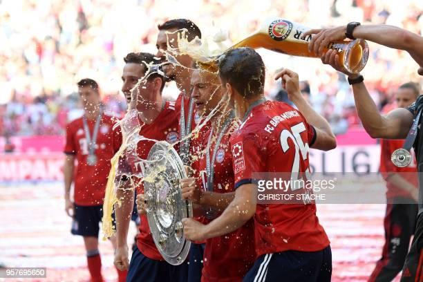 Bayern Munich's German midfielder Sebastian Rudy forward Sandro Wagner German midfielder Joshua Kimmich and German forward Thomas Mueller are doused...
