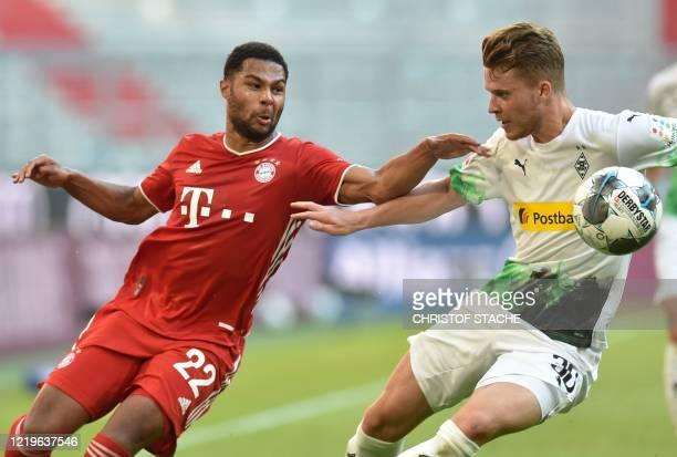 Bayern Munich's German midfielder Serge Gnabry and Moenchengladbach's Swiss defender Nico Elvedi vie for the ball during the German first division...