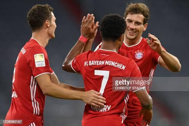 Bayern Munich's German midfielder Serge Gnabry celebrates scoring with his teammate Bayern Munich's French defender Benjamin Pavard and Bayern...
