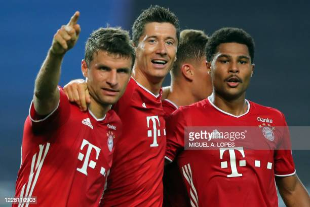 TOPSHOT Bayern Munich's German midfielder Serge Gnabry celebrates with Bayern Munich's German forward Thomas Mueller and Bayern Munich's Polish...