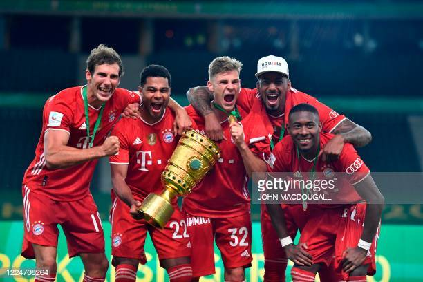 Bayern Munich's German midfielder Serge Gnabry holds the German Cup trophy as he and his teammates celebrate winning the final football match Bayer...