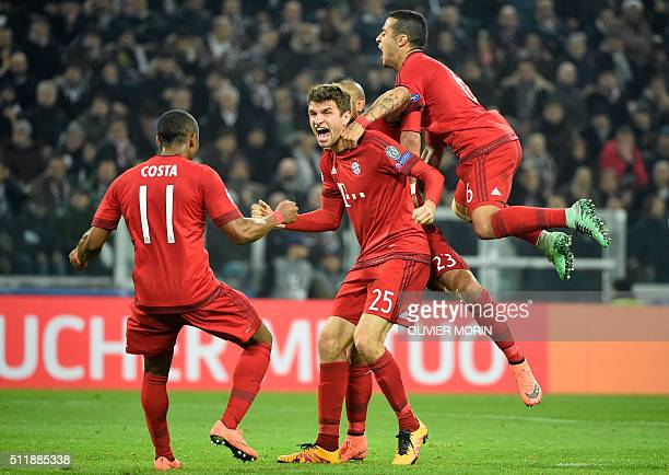 Bayern Munich's German midfielder Thomas Mueller celebrates with teammates after scoring a goal during the UEFA Champions League round of 16 first...