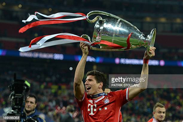 Bayern Munich's German striker Mario Gomez celebrates with the trophy on the pitch after their victory in the UEFA Champions League final football...