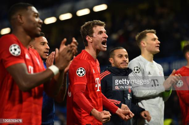 Bayern Munich's German striker Thomas Mueller and teammates celebrate their win with their supporters after the UEFA Champion's League round of 16...