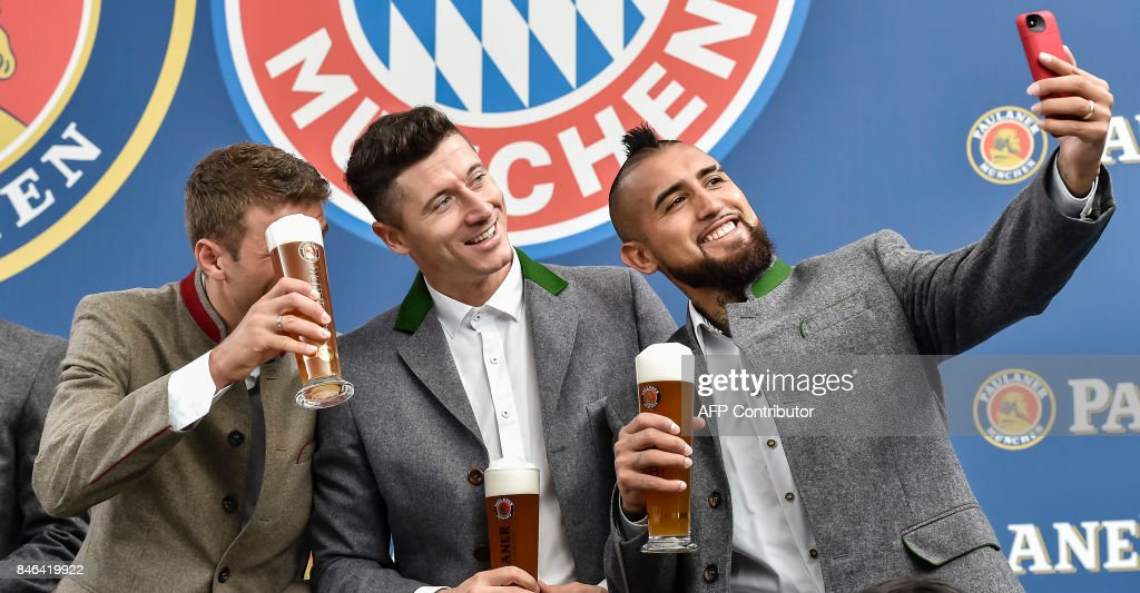 Bayern Munich's German striker Thomas Mueller, Bayern Munich's Polish striker Robert Lewandowski and Bayern Munich's Chilian midfielder Arturo Vidal gratulate Thomas Mueller to his birthday and pose for a selfie during a photo shooting for a FC Bayern Munich sponsor in traditional bavarian clothing in Munich, southern Germany, on September 13, 2017. /