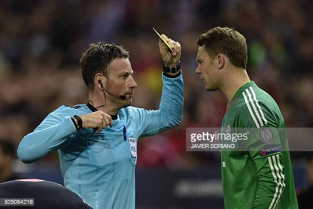 Bayern Munich's goalkeeper Manuel Neuer is cautioned with a yellow card during the UEFA Champions League semifinal first leg football match Club...
