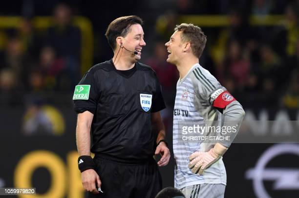Bayern Munich's goalkeeper Manuel Neuer jokes with referee Manuel Graefe during the German first division Bundesliga football match BVB Borussia...