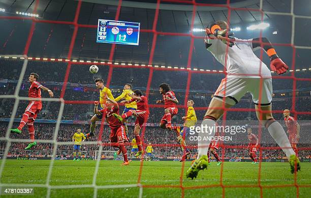 Bayern Munich's goalkeeper Manuel Neuer saves a header from Arsenal's French forward Olivier Giroux during the second-leg round of 16 UEFA Champions...