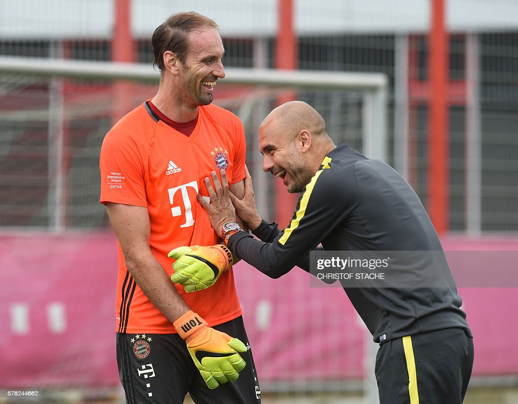 Bayern Munich's goalkeeper Tom Starke (L) welcomes his former coach and now Manchester's headcoach Pep Guardiola (R) after a team training of Bayern Munich and ahead a team training session of Manchester City at the training ground of the German first division football team FC Bayern Munich in Munich, southern Germany, on July 21, 2016. / AFP / CHRISTOF