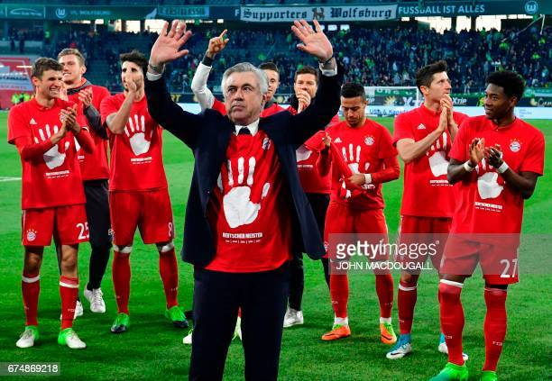 Bayern Munich's Italian head coach Carlo Ancelotti and his team celebrate becoming the new German champion after the German first division Bundesliga...