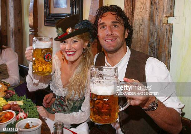 Bayern Munich's Italian striker Luca Toni, dressed in traditional Bavarian clothes , and his girlfriend Italian model Marta Cecchetto cheer with beer...