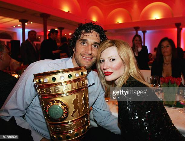 Bayern Munich's Italian striker Luca Toni poses with his girlfriend Italian model Marta Cecchetto and the German Cup trophy on early April 20 2008...