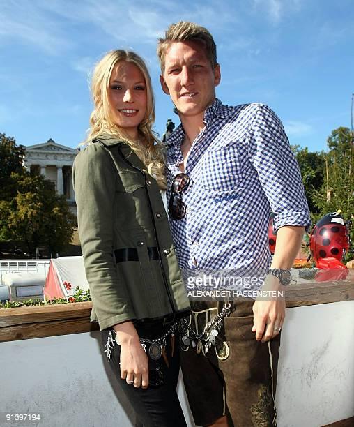 Bayern Munich's midfielder Bastian Schweinsteiger and his girlfriend Sarah Brandner dressed in traditional Bavarian clothes pose at the Oktoberfest...