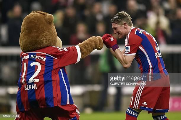 Bayern Munich's midfielder Bastian Schweinsteiger jokes with mascot Berni during the German first division Bundesliga football match FC Bayern...