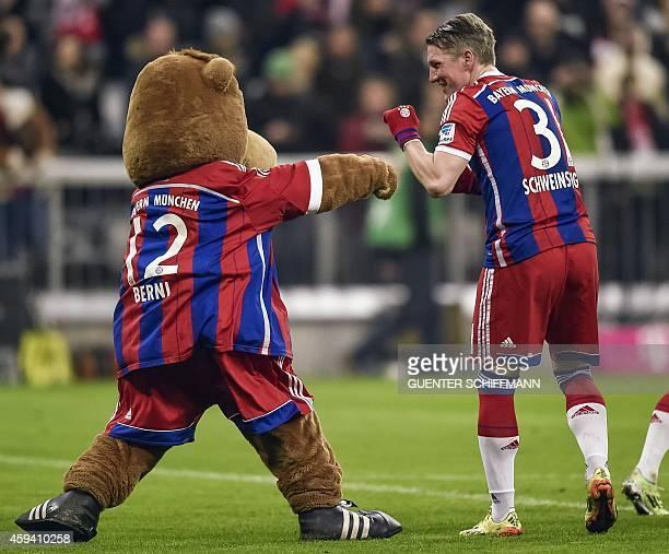 Bayern Munich's midfielder Bastian Schweinsteiger jokes with mascot Berni after the German first division Bundesliga football match FC Bayern...