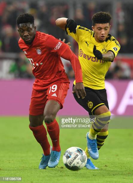 Bayern Munich's midfielder Davies Alphonso and Dortmund's Great Britain midfielder Jardon Sancho vie for the ball during the German first division...