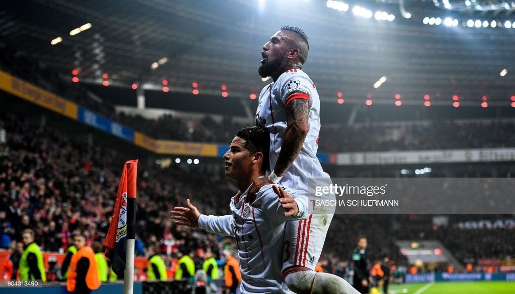 Bayern Munich's midfielder James Rodriguez celebrates after scoring with Bayern Munich's Chilean midfielder Arturo Vidal (R) during the German First division Bundesliga football match Bayer Leverkusen vs FC Bayern Munich on January 12, 2018 in Leverkusen, western Germany. /